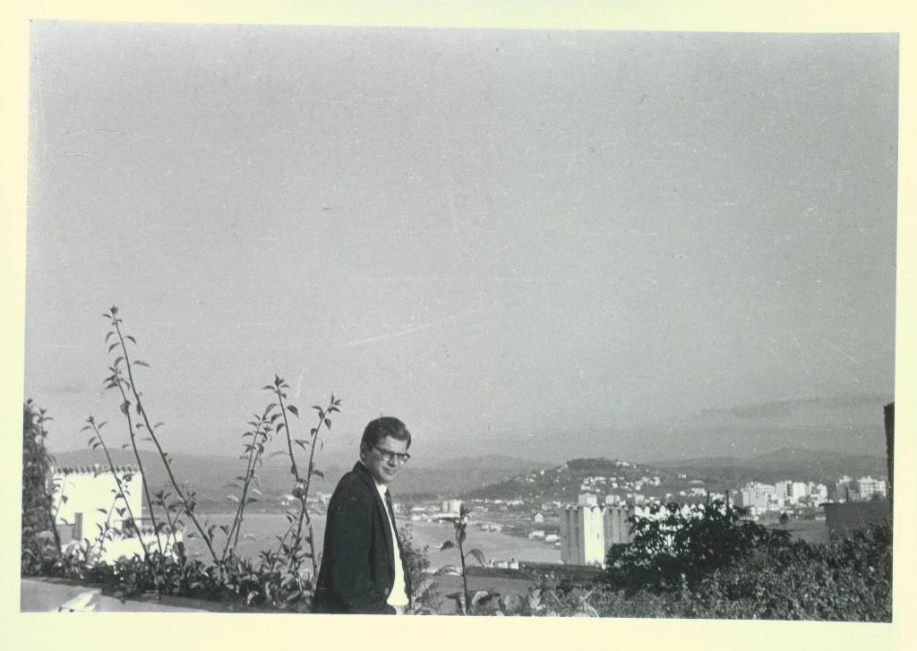 Allen Ginsberg in in black suit jacket, backdrop Tangier